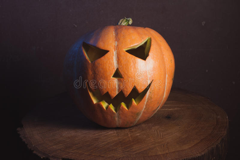 Jack-o ' - lantern in warm tones. On a wooden background, three-dimensional and bright light stock images