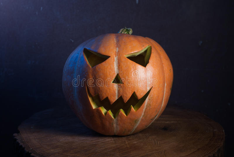 Jack-o ' - lantern in warm tones. On a wooden background, three-dimensional and bright light royalty free stock photos