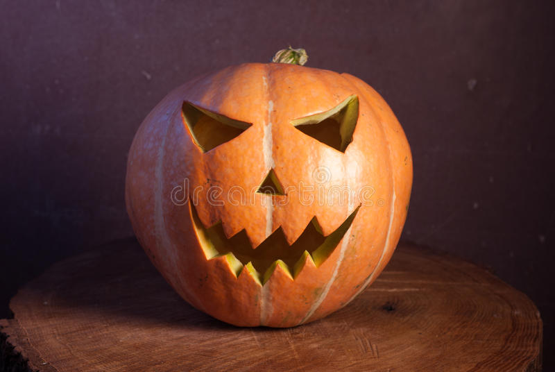 Jack-o ' - lantern in warm tones. On a wooden background, three-dimensional and bright light royalty free stock photography
