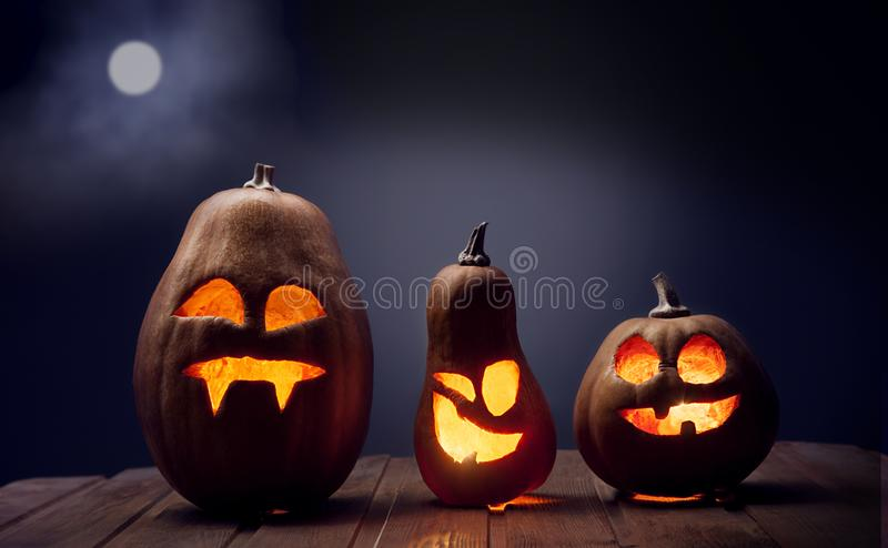 Jack o lanterns Halloween pumpkin face on wooden background. And autumn leafs stock photos