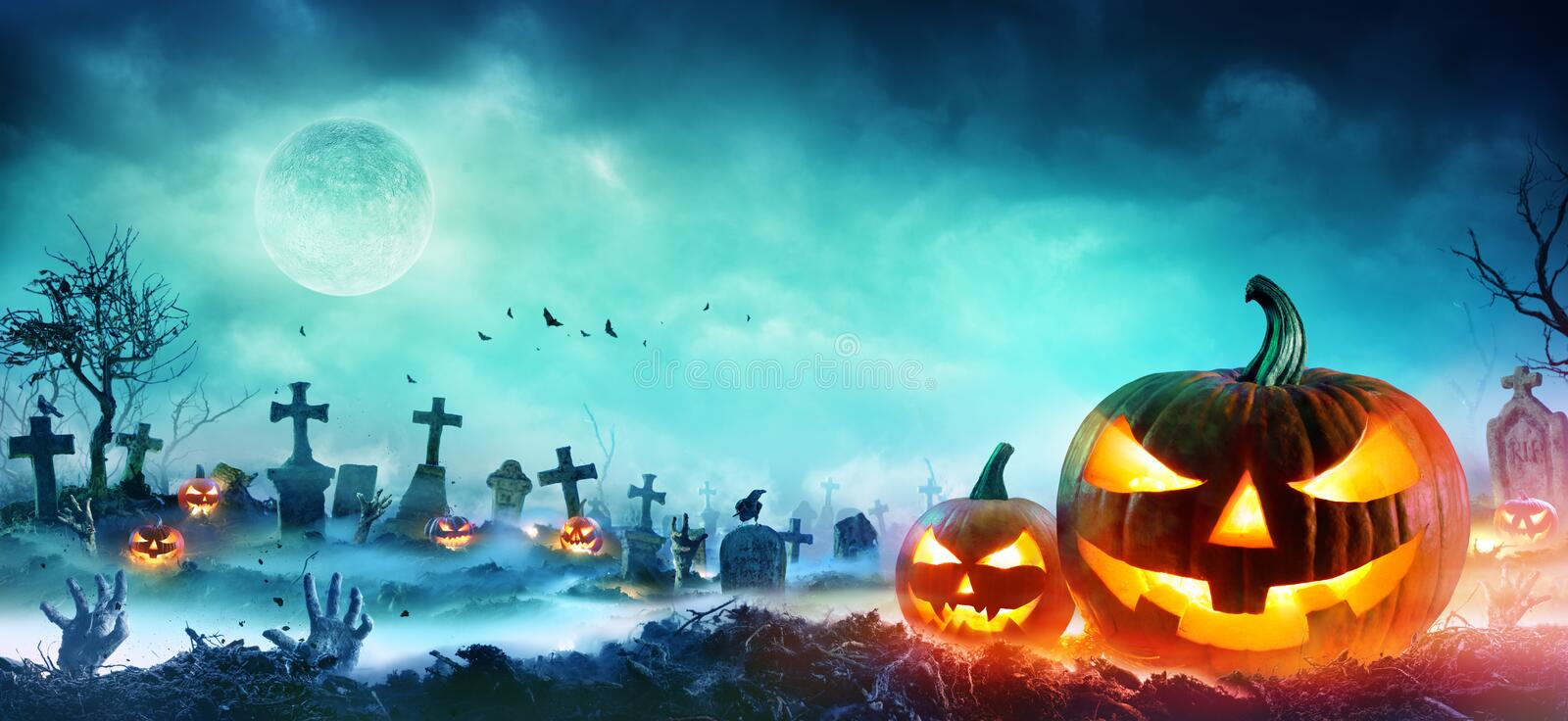 Jack O Lanterns And Zombie Hands Rising Out Of A Graveyard royalty free stock photography