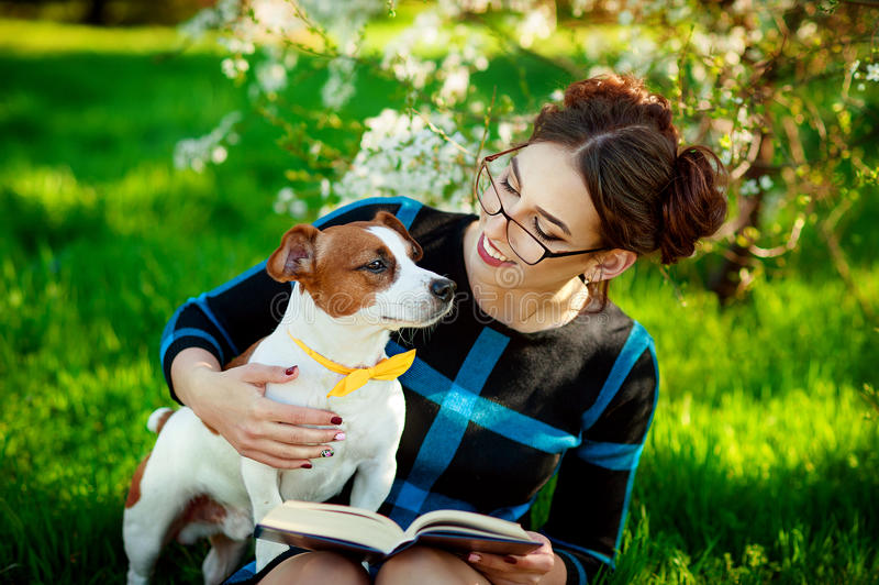 Jack Russell Terrier dog with owner woman playing in the spring outdoors. Modern Youth Lifestyle Concept. stock photos