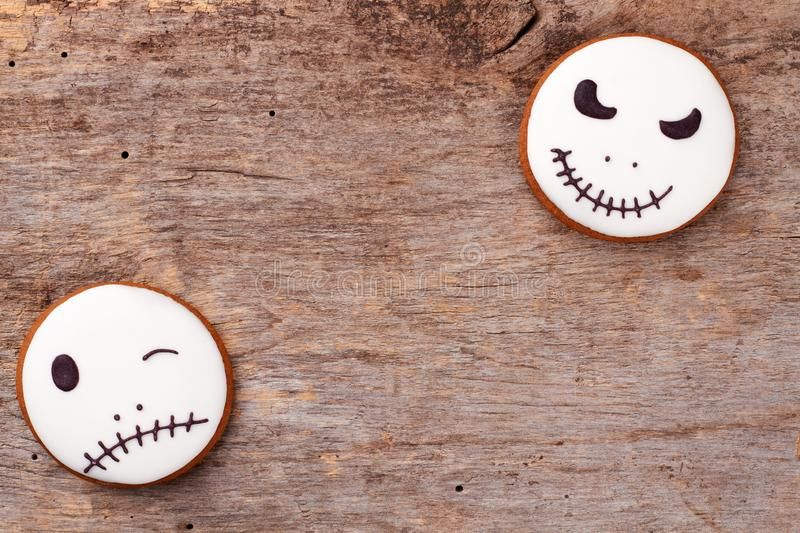 Jack Skellington cookies and copy space. White ginger biscuits with Halloween faces on old wooden background. Trick or treat concept royalty free stock images