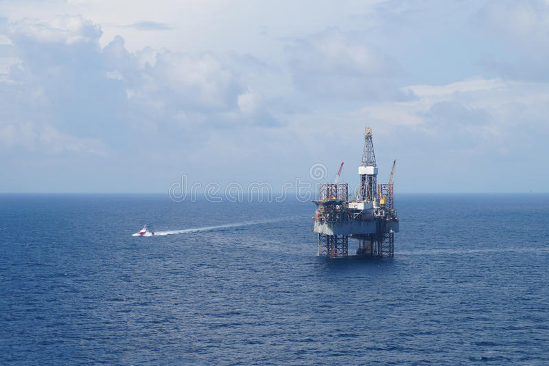 Jack up oil drilling rig and a crew boat royalty free stock photography