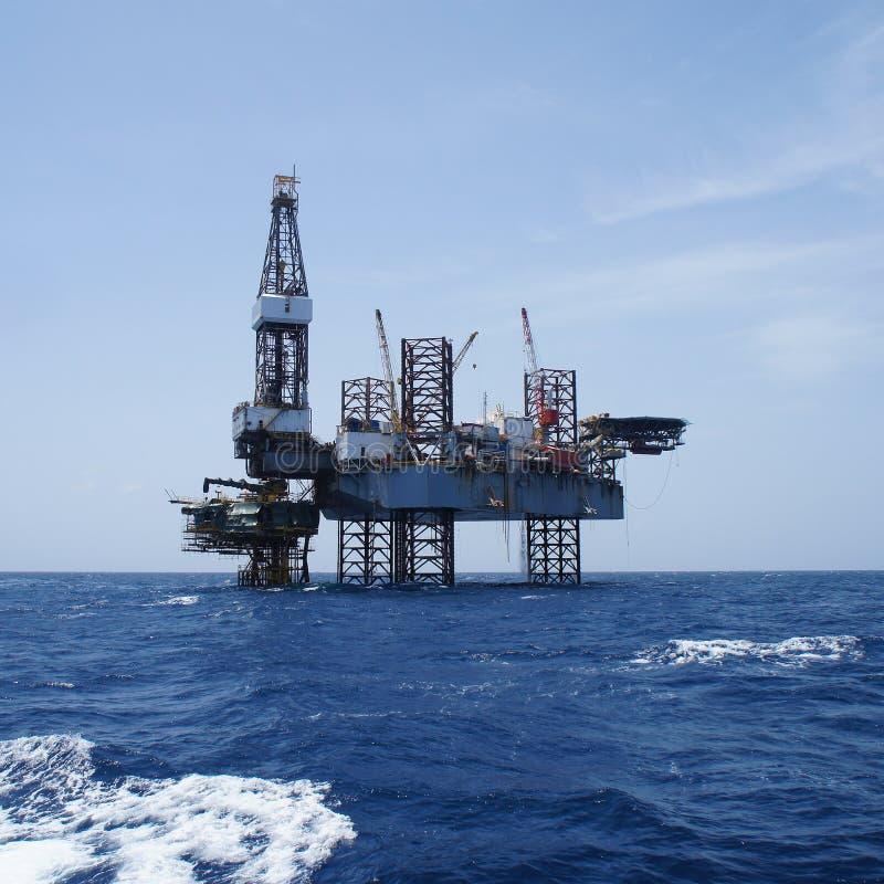Jack Up Oil Drilling Rig a pouca distância do mar e a plataforma da produção imagem de stock