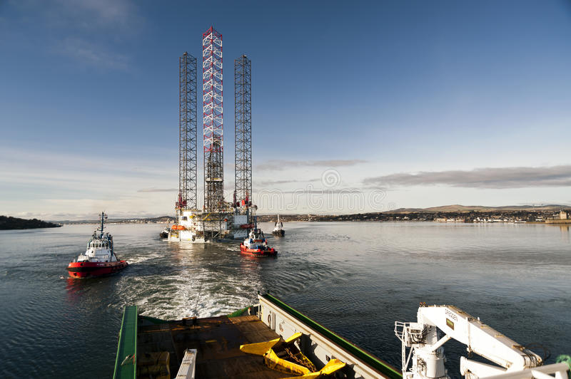 Jack-up rig Ensco 120 in the entrance channel of Dundee, United Kingdom. 01.12.2013 Tug boats towing the rig Ensco 120 out from Dundee in UK royalty free stock image