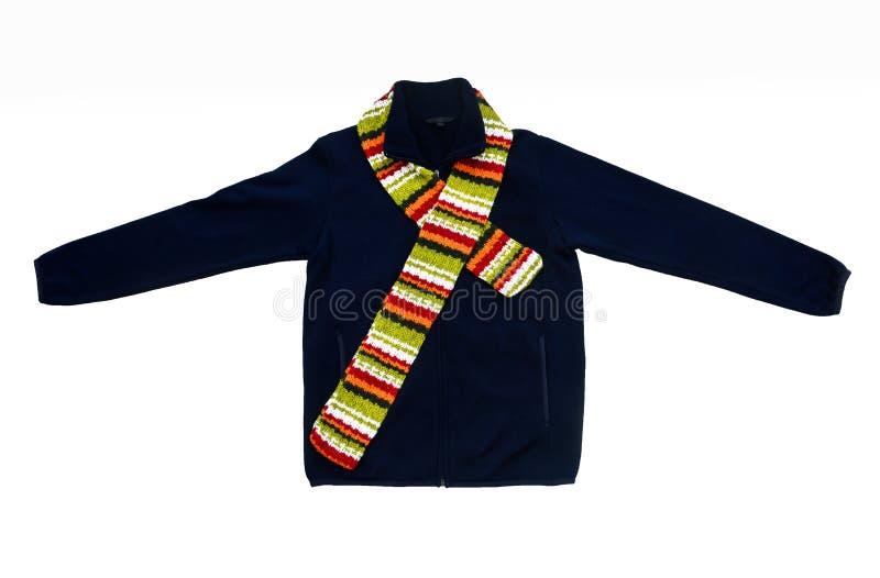 Jacke des dunkelblauen Vlieses im Freien mit buntem gestricktem Schal auf weißem Hintergrund lizenzfreie stockfotografie