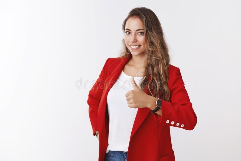 Jacken-Vertretungsdaumen der netten gelockten kaukasischen Zähne der Frau weißen lächelnder tragender roter modischer oben wie Zu lizenzfreie stockbilder