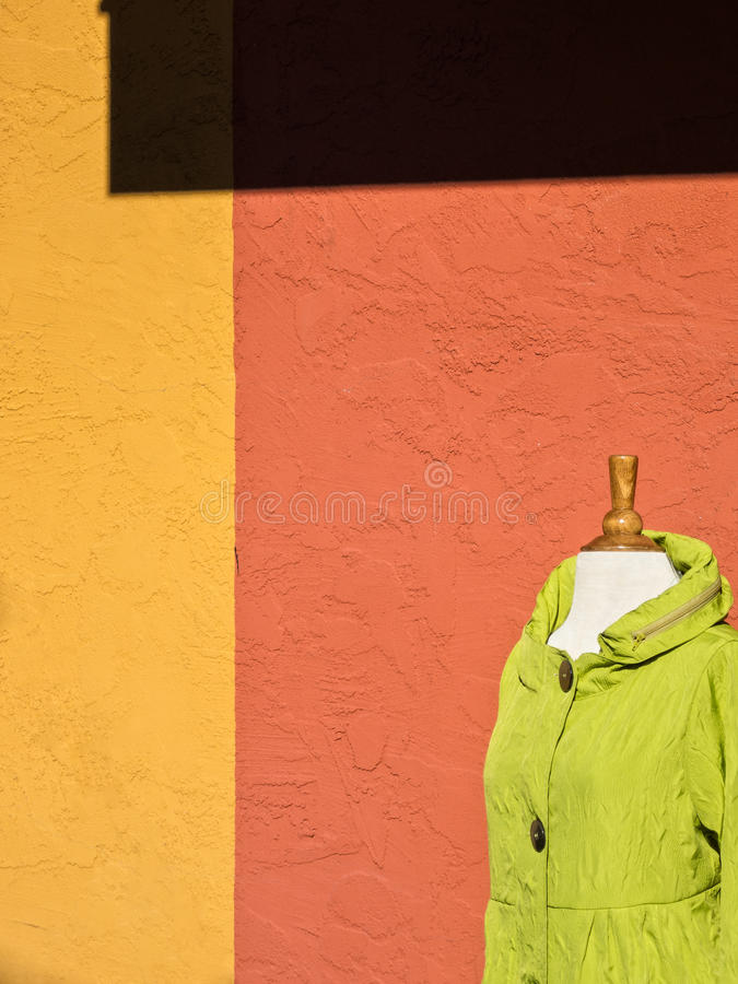 Jacket on sale, plenty of color. Colorful wall and jacket outside a boutique stock photography