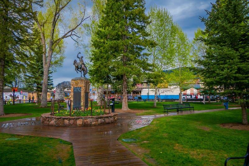 JACKSON HOLE, ΟΥΑΪΌΜΙΝΓΚ, ΗΠΑ - 23 ΜΑΐΟΥ 2018: Υπαίθρια άποψη του περπατήματος τουριστών σε ένα πάρκο κοντά σε ένα άγαλμα χαλκού  στοκ φωτογραφία