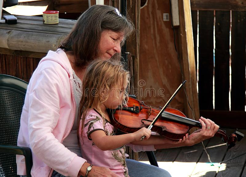 Woman and little girl playing violin on Acoustic Music Festival in Florida. stock photos