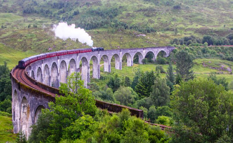 The Jacobite steam train, aka `Hogwarts Express in Harry Potter movies` passes Glenfinnan viaduct, Scotland, UK. On a summer cloudy day royalty free stock photo
