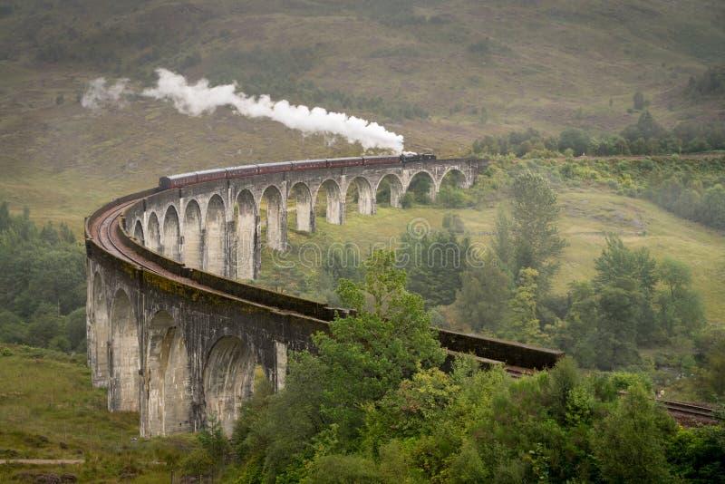 Jacobite steam train, a.k.a. Hogwarts Express, passes Glenfinnan royalty free stock photo