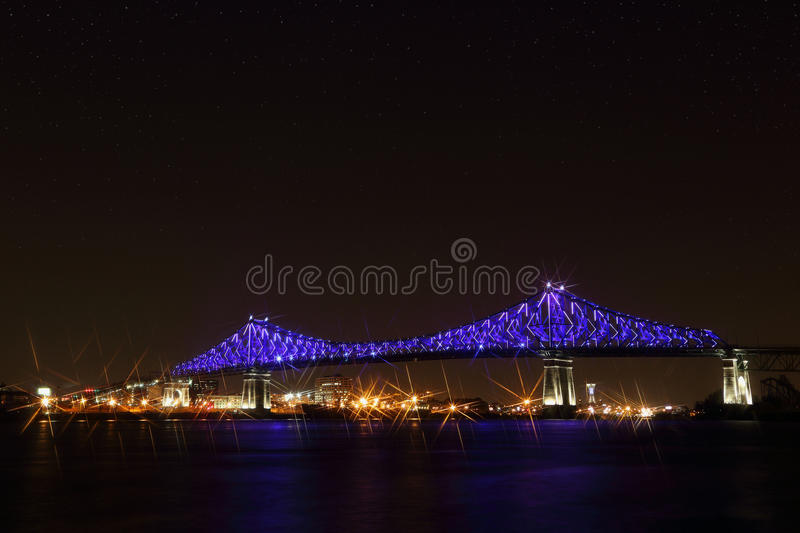 Jacques Cartier Bridge Illumination in Montreal, reflection in water. Montreal's 375th anniversary. Luminous colorful interactive Jacques Cartier Bridge stock photo
