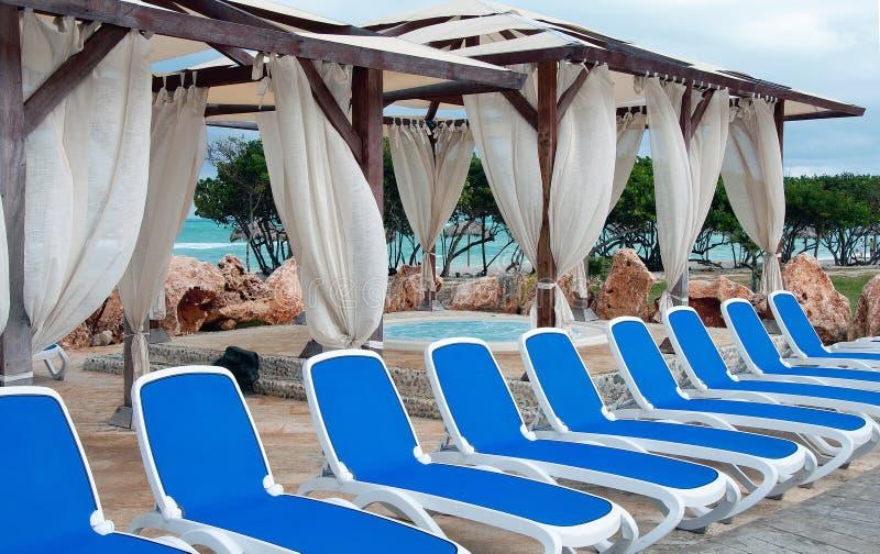Jacuzzi en blauwe sunbeds in de Caraïben stock afbeeldingen