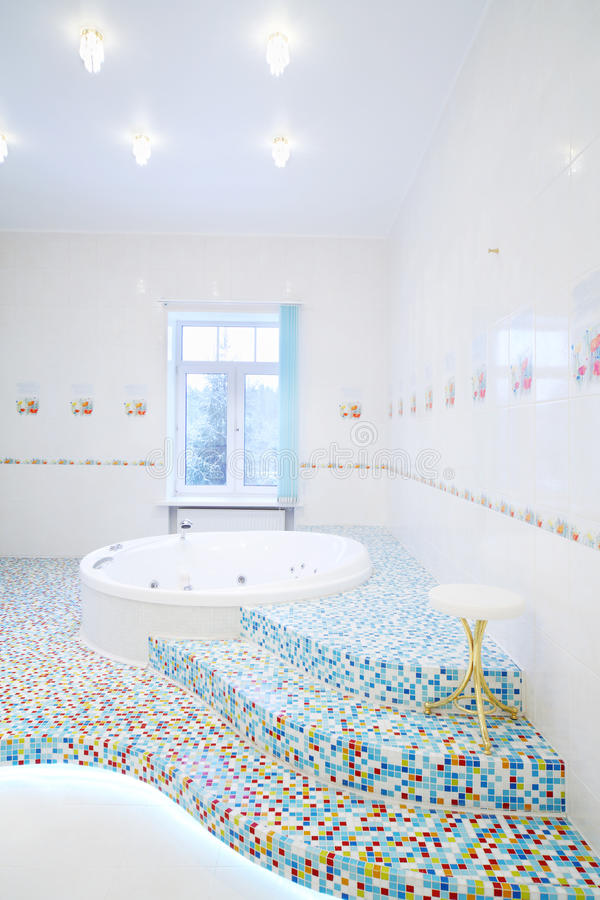 Jacuzzi en treden in ruime witte badkamers stock afbeeldingen