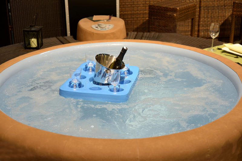 Jacuzzi, hot tub. For recreation and luxury relaxation. A tablet with champagner and glasses is swimming on the top of the whirling water. Image for luxury royalty free stock photography