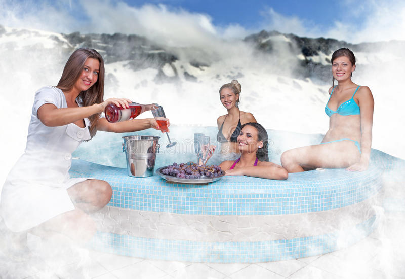 Jacuzzi serve. Womans relaxing in jacuzzi and serve champagne from waiter royalty free stock photos