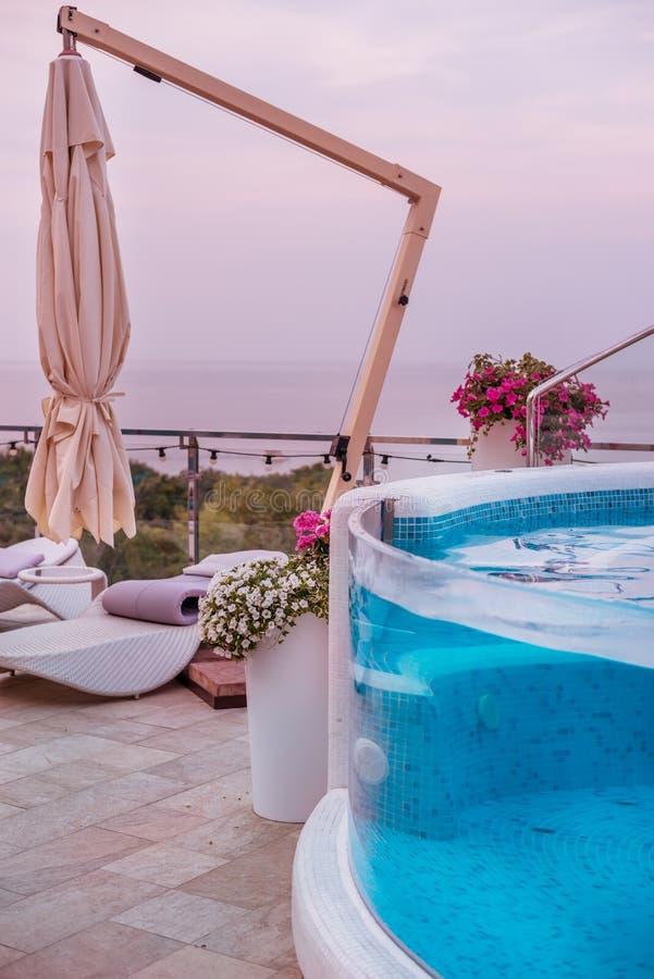 Jacuzzipool en comfortabel plaatsingsgebied met zonlanterfanters door de pool stock foto's