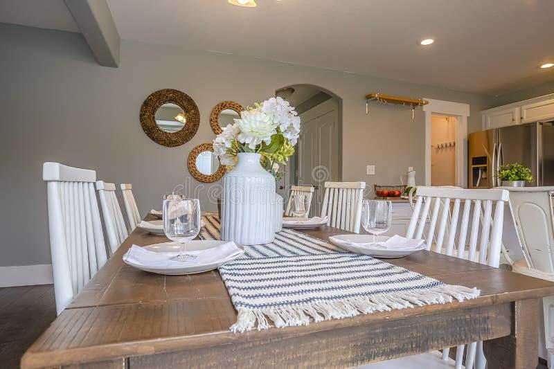 Jadalni wnętrze z brązu stołu i białych drewnianymi drewnianymi krzesłami zdjęcie stock