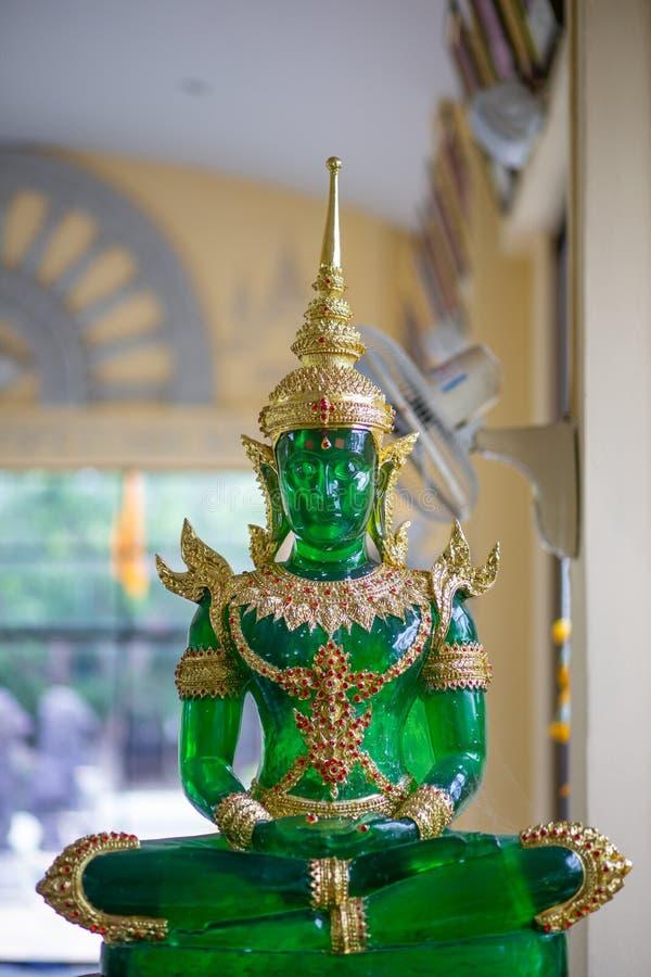 Jade Buddha med grönt och guld- sammanträde på bakgrund royaltyfria foton