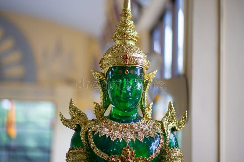 Jade Buddha med grönt och guld- sammanträde på bakgrund arkivbilder