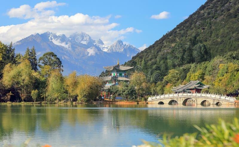 Jade Dragon Snow Mountain och bro på svarta Dragon Pool Lijiang, Yunnan Kina arkivbilder