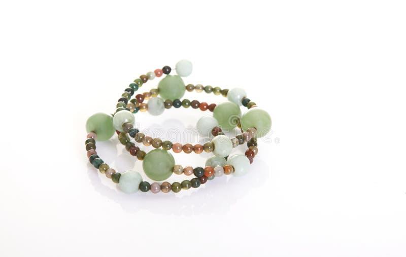 Jade och mång- färggemstonearmband på vit bakgrund arkivfoton