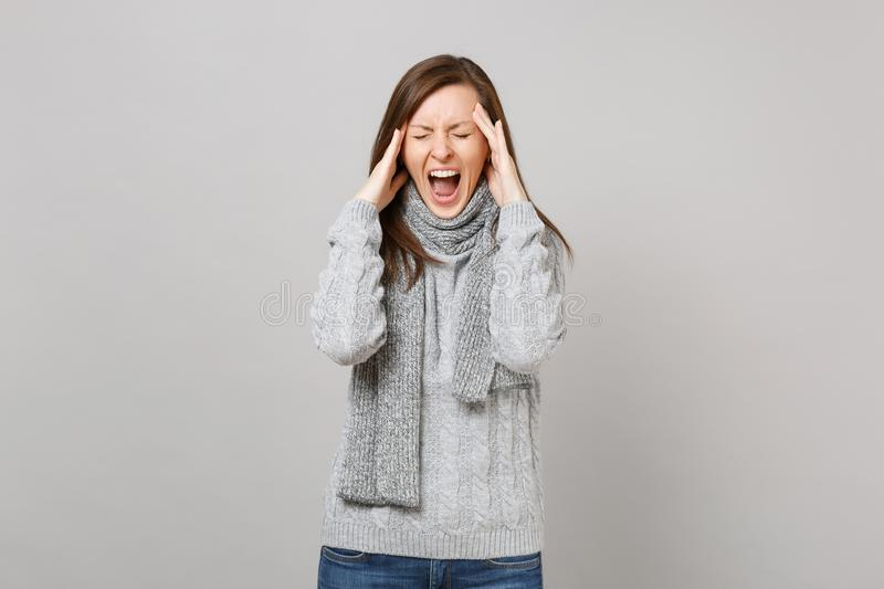 Jaded young woman in gray sweater, scarf with closed eyes screaming putting hands on head having headache on royalty free stock photos