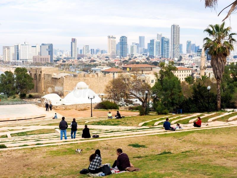 Jaffa, Israël - Februari 4, 2017: Mensen die op het gazon ontspannen en de mening van de promenade van Tel Aviv bewonderen royalty-vrije stock fotografie