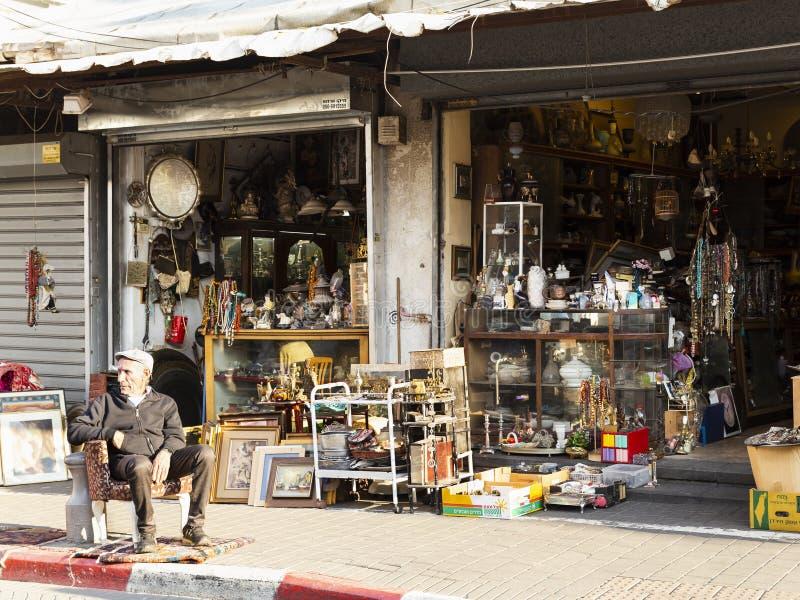 Jaffa viejo, Tel Aviv, Israel - 23 de diciembre de 2018: Un viejo vendedor que se sienta en butaca delante de su anticuario en pu fotos de archivo libres de regalías