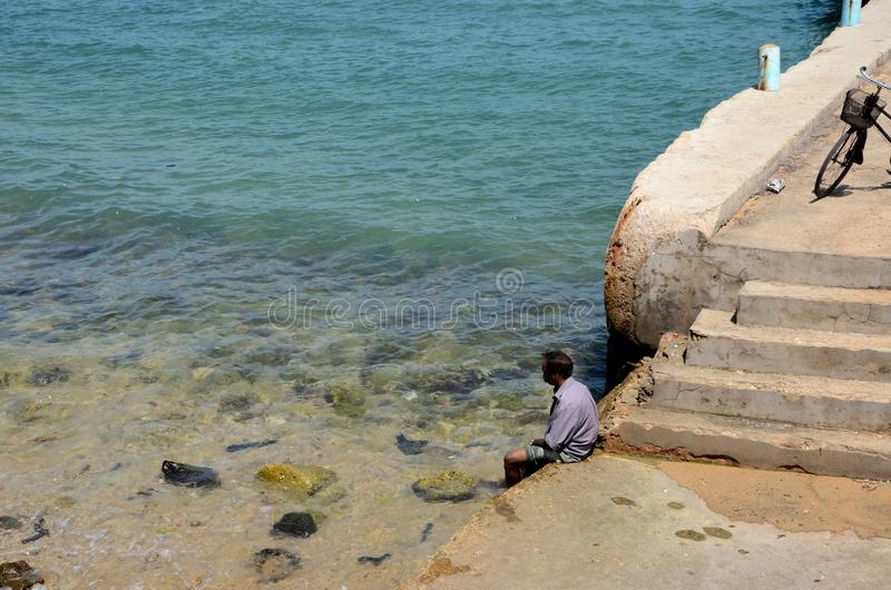 Man dips feet in water at beach pier near steps in Jaffna Sri Lanka. Jaffna, Sri Lanka - February 19, 2017: A sri Lankan fisherman dips his feet in the Indian stock photos