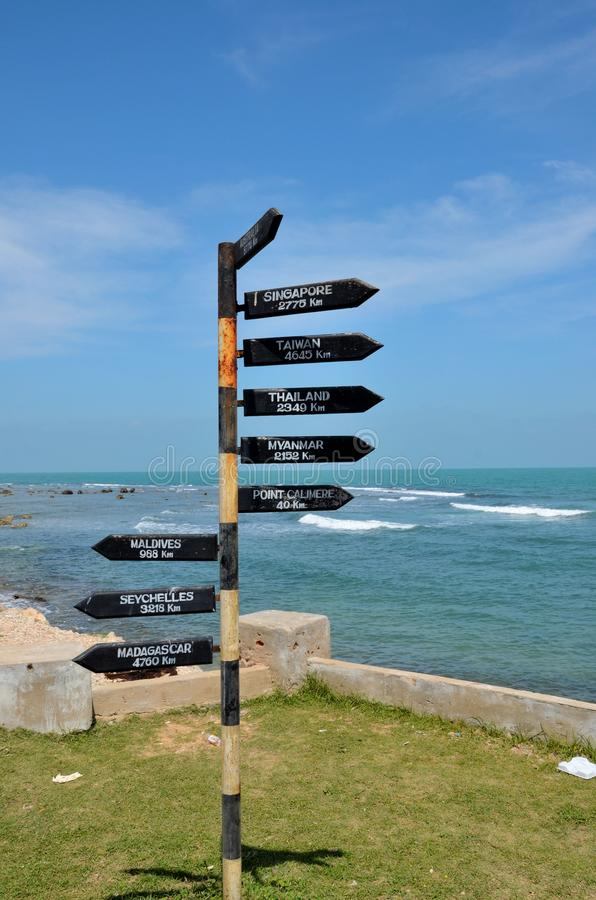 Directional distance arrows with kilometers to Australia & Singapore at beach in Jaffna Sri Lanka. Jaffna, Sri Lanka - February 19, 2017: Six arrown located near royalty free stock photo