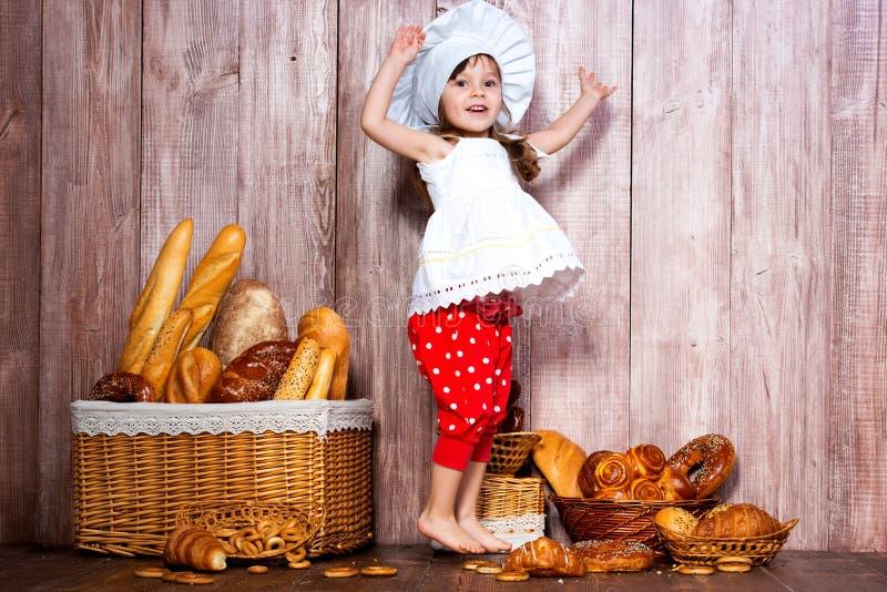 Jag älskar bullar Liten le flicka i ett laga mat lock som hoppar för glädje och fröjd nära en vide- korg med brödrullar och bager royaltyfri bild