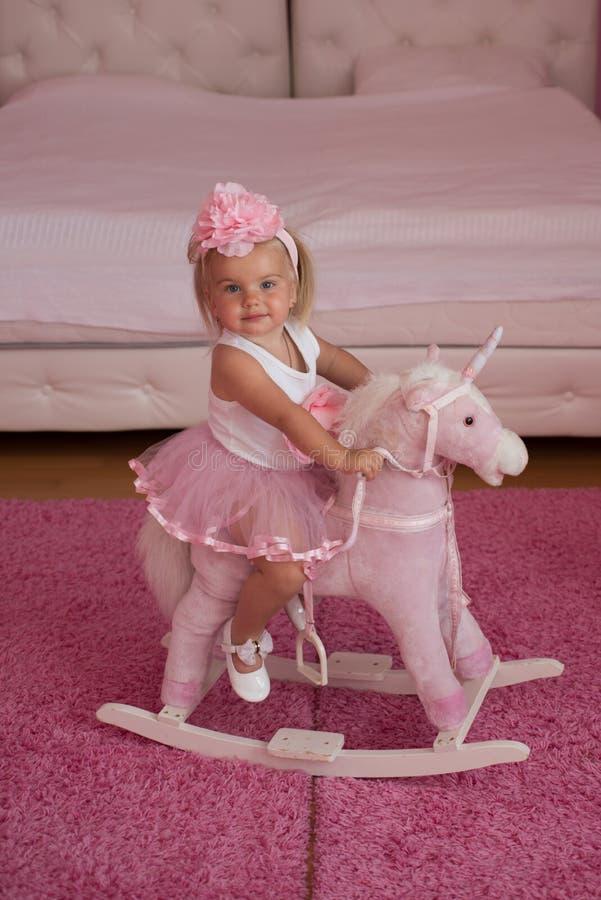 Jag älskar denna häst Liten blond häst för flickarittleksak Musikband för småbarnkläderhår Liten flicka med den långa frisyren hå royaltyfria foton