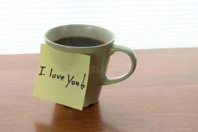 Jag älskar dig! anmärkning på att ånga koppen kaffe i morgonljus royaltyfri fotografi