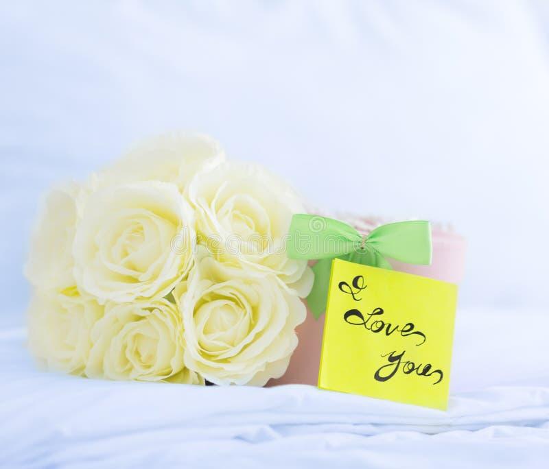 Jag älskar dig! Härlig gåvaask och rosor på en säng man för begreppskyssförälskelse till kvinnan arkivfoto