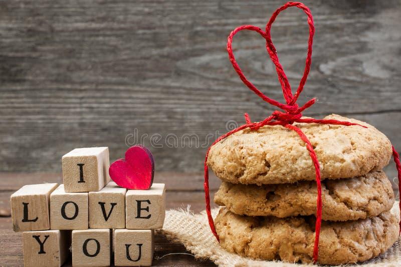 Jag älskar dig inskriften med trähjärta och högen av hemlagade kakor arkivfoton