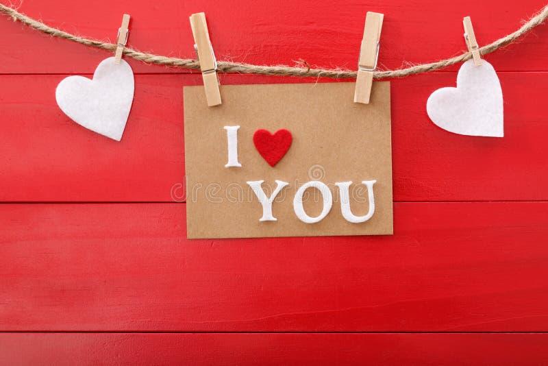 Jag älskar dig meddelandekortet över rött träbräde arkivfoton