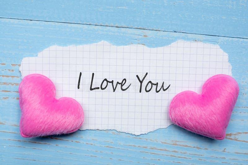 JAG ÄLSKAR DIG ordet på pappers- anmärkning med för hjärtaform för par rosa garnering på blå trätabellbakgrund Gifta sig romantis arkivbild