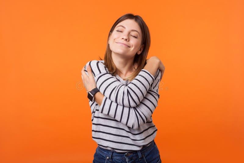Jag älskar mig själv! Porträtt av en mjuk, vacker kvinna med brunt hår i en lång skjorta Inomhusstudio isolerad på fotografering för bildbyråer