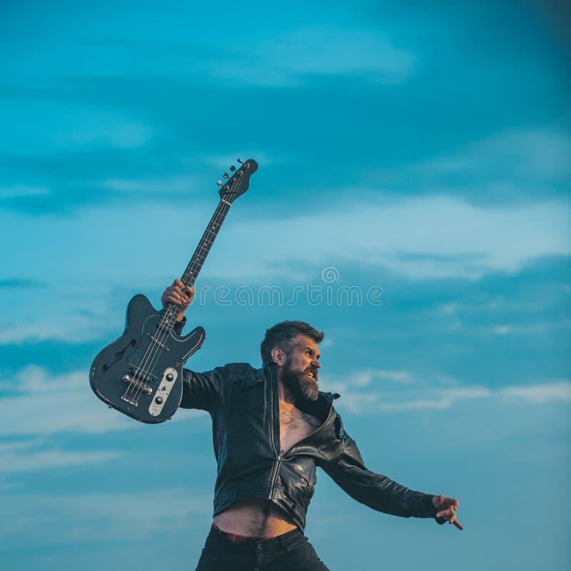 Jag älskar min gitarr Den skäggiga mannen hoppar med gitarren på blå himmel Hipstergitarrist med skägget på upphetsad framsidaflu royaltyfri bild
