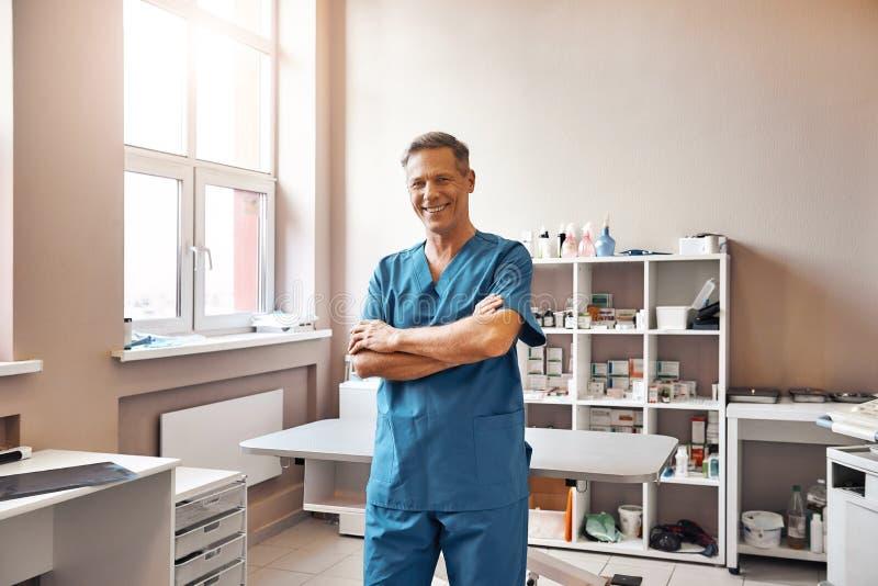 jag älskar mitt arbete Gladlynt mellersta åldrig veterinär, i enhetligt anseende för arbete med korsade armar och att le på den v royaltyfri bild