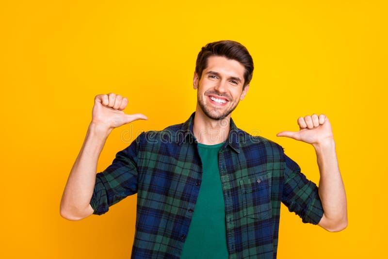 Jag är bäst Foto av en fantastisk kille som visar tumfingrarna på sig själv och bär en lätt schockad skjorta med isolerad gul fär arkivbild
