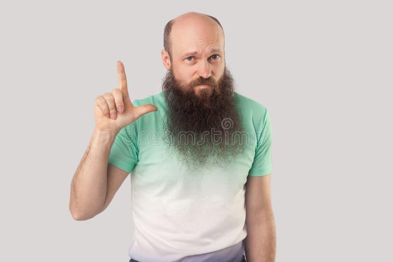 Jag är förloraren Stående av den åldriga skalliga mannen för ledsen mitt med det långa skägget i ljust - grönt t-skjorta anseende arkivfoton