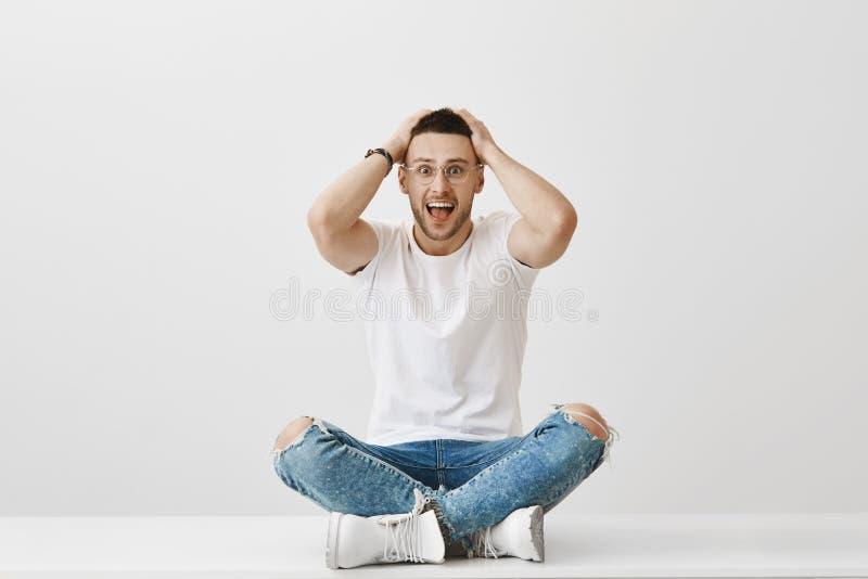 Jag är så lycklig dig är här Studioskott av den attraktiva skämtsamma europeiska mannen med borstet som sitter på golv med korsat arkivfoto