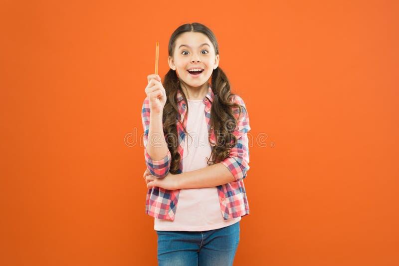 Jag ?r snillen Flickasnille Fick den lilla skolflickan f?r snille en ljus id? p? orange bakgrund Sm?barn som pekar pennan royaltyfri foto