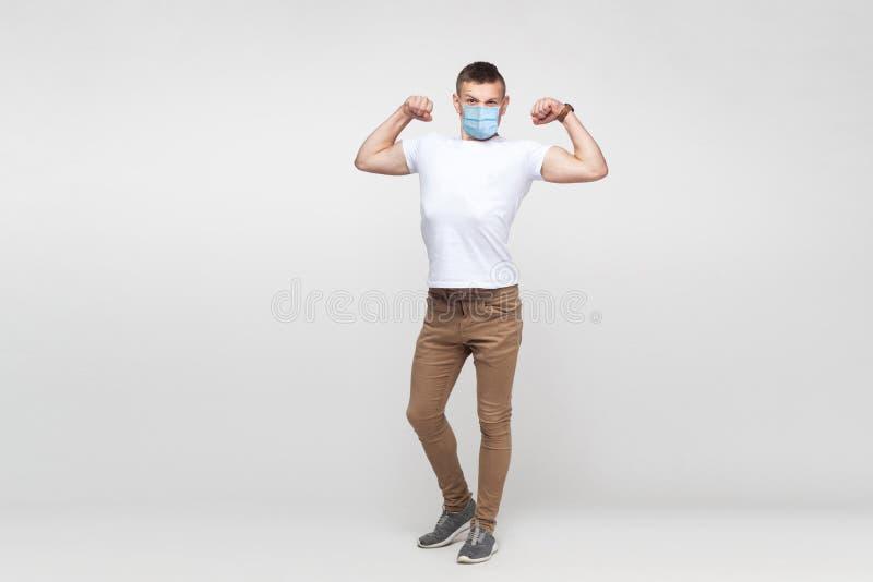 Jag är stark Fullständig porträtt av ung man i vit skjorta med operationsmasken stående och med biceps och royaltyfria foton