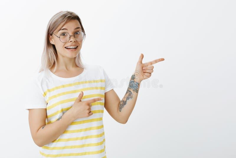 Jag önskar show dig något utmärkt Stående av den lyckliga charmiga kvinnan med ganska hår och tatueringar som i huvudsak ler meda arkivfoto