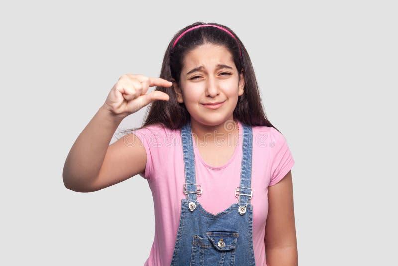 Jag behöver få mer Stående av bekymmerbrunettunga flickan i rosa t-skjorta och blåa overaller som står med liten gest med fingrar royaltyfri foto